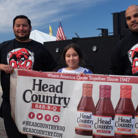 Three people at bbq festival holding up head country sign